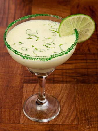 fresh cocktail served on a bar top garnished with green sugar and a lime wheel photo
