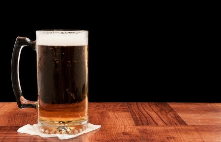 mug of ale: light pilsner served in a frosted mug isolated on a black backgound Stock Photo