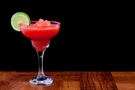 strawberry margarita isolated on a black background served on a bar top photo
