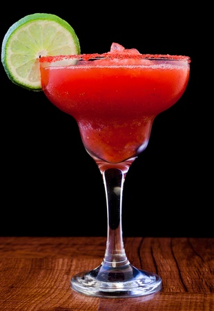 frozen fruit: strawberry margarita isolated on a black background served on a bar top