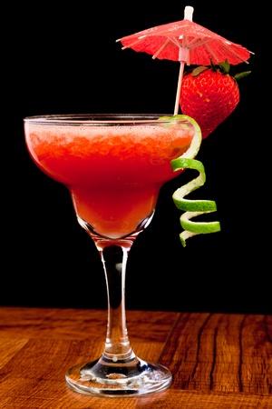 fresh pureed strawberry margarita isolated on a black background photo