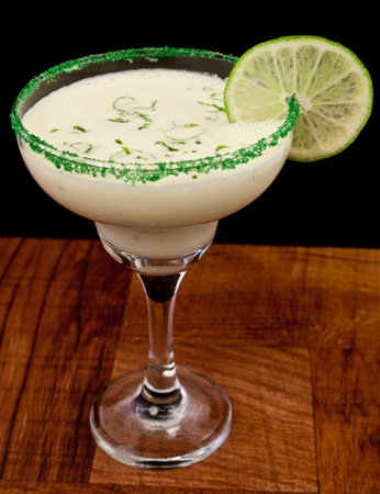 fresh cocktail served on a bar top garnished with green sugar and a lime wheel isolated on a black background photo