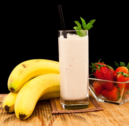 milk shake: fresh strawberry banana banana milk shake on a tropical mat isolated on a black background Stock Photo
