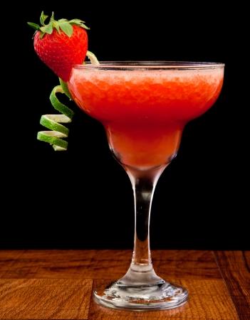 fresh pureed strawberry margarita isolated on a black background
