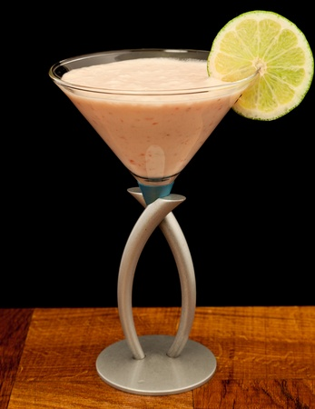pureed strawberries and bananas in a martini glass garnished with a lime wheel photo