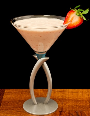 strawberry shake in a martini glass garnished with a fresh sliced strawberry isolated on black photo