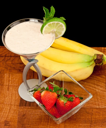 strawberry banana cocktail with fresh fruit and mint garnish isolated  on black background photo