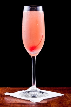 alcoholic drink: pink champagne cocktail with a cherry isolated on a black background
