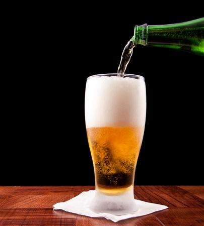 vasos de cerveza: vertiendo una botella de cerveza en un vaso fr�o aislado en un fondo negro Foto de archivo
