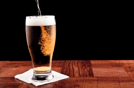 light beer on a bar top isolated on a black background Stock Photo - 13066596