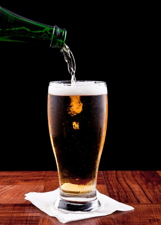 filling bottles: bottle pouring a beer into a chilled glass isolated on a black background