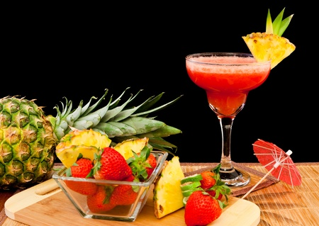fresh tropical fruit cocktail on a bar top isolated on a black background photo