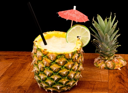 fresh tropical pina colada cocktail served in a pineapple photo