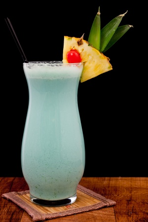 blue hawaiian cocktail isolated on a black background served on a bar top photo