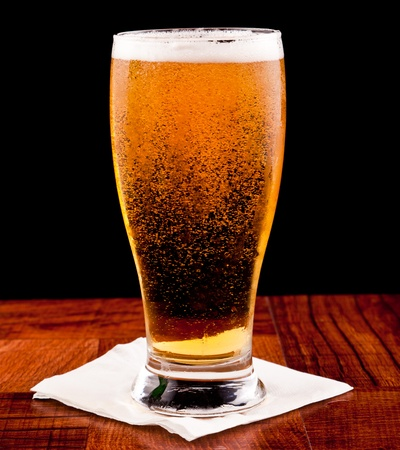 light beer on a bar top isolated on a black background Stock Photo - 13233089