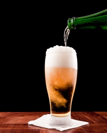 fles gieten van een biertje in een gekoeld glas geà ¯ soleerd op een zwarte achtergrond