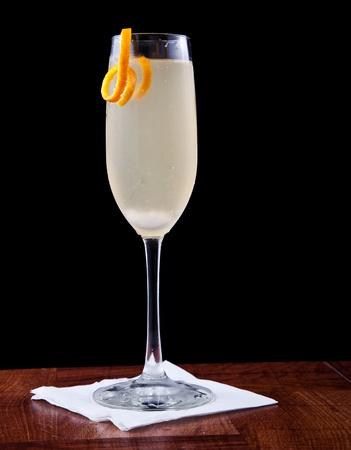 cocktail di champagne serviti su un piano bar isolato su nero guarnito con un tocco d'arancia Archivio Fotografico