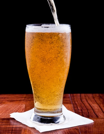 light beer on a bar top isolated on a black background Stock Photo