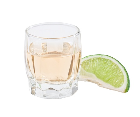 shot of tequila with a green lime isolated on a white background