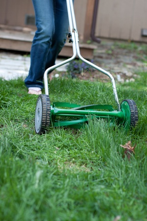 out of focus female shoes pushing a mower cutting grass in the back yard photo