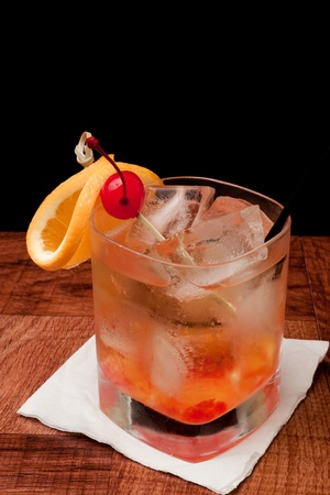 whiskey old fashioned with cherries and orange isolated on a black background
