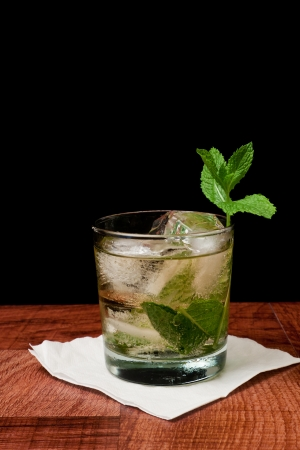 Mint julep isolated on a black background served on a bar top garnished with fresh mint Stock Photo