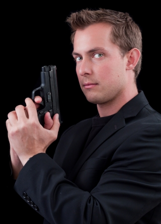 caucasian male model holding a gun isolated on a black background Stock Photo