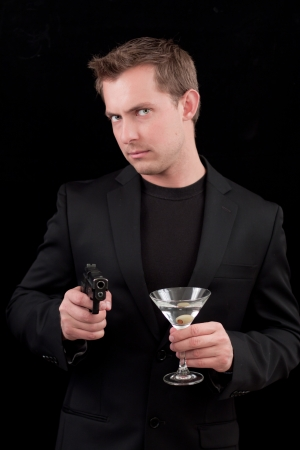 caucasian male model holding a gun isolated on a black background Stock Photo - 13991357