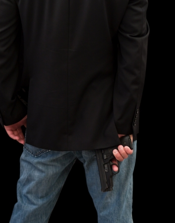 man holding gun: back of a male with a gun dressed with sports jacket with a gun Stock Photo