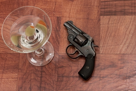 closeup of an old hand gun on a table with a martini out of focus photo