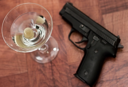 closeup of a martini on a bar top with an out of focus gun photo
