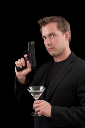 caucasian male model holding a gun isolated on a black background Stock Photo - 13991360