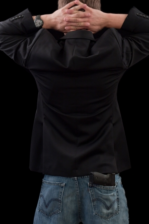 back of a male with a gun dressed with sports jacket with a gun photo