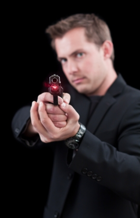 Young man pointing a gun with a laser only the front of the gun in focus photo