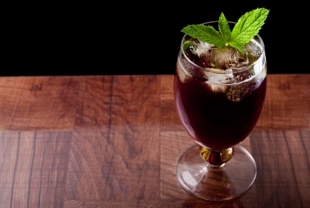 sweet iced tea on a bar top isolated on a black background garnished with fresh mint photo