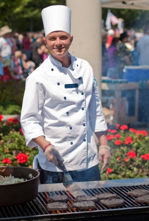 grill: smiling chef cooking burgers outdoors on a nice summer day