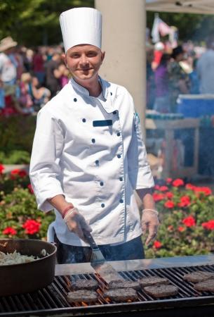 chef cocinando: sonriente chef de cocina al aire libre, hamburguesas en un agradable d�a de verano