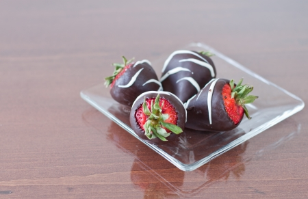 four strawberries covered in dark cholate served on a clear plate Stock Photo