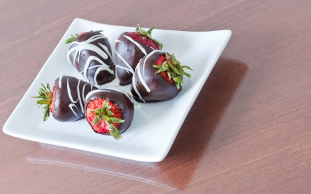 five chocolate covered strawberries served on a white plate photo