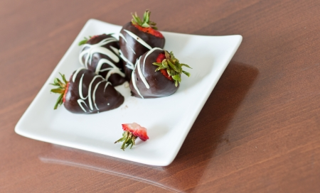 four chocolate covered strawberries on a white plate, focus on the stem of a tasty one photo