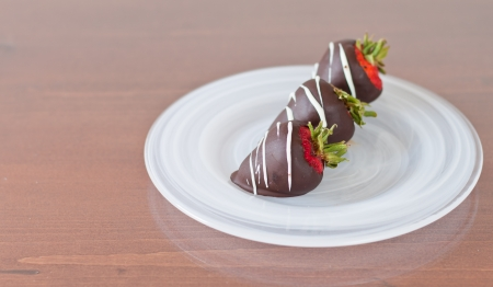 Three chocolate covered strawberries on a white plate served for dessert photo