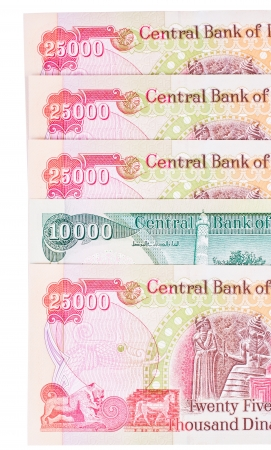 a broken pattern of 25 thousand iraqi dinar notes with a 10 thousand note, isolated on a white background photo
