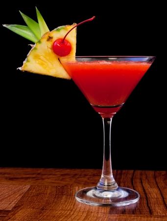 alcoholic drink: tropical cocktail isolated on a black background served on a bar top Stock Photo