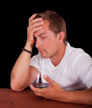 young man at a bar holding his head and drinking wine photo