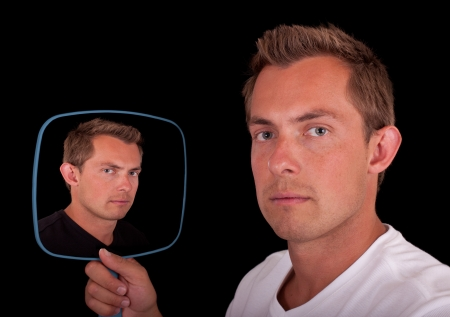 Concept of a dual personality mirror reflection of a young man isolated on a black background Stockfoto
