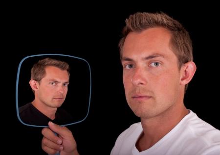 spiegels: Concept van een dubbele persoonlijkheid spiegeling van een jonge man geïsoleerd op een zwarte achtergrond Stockfoto