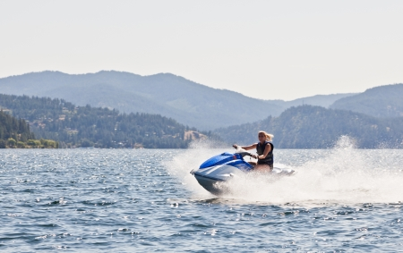 Beautiful woman out on the lake riding a wave runner on bright sunny day Stock Photo - 15199332
