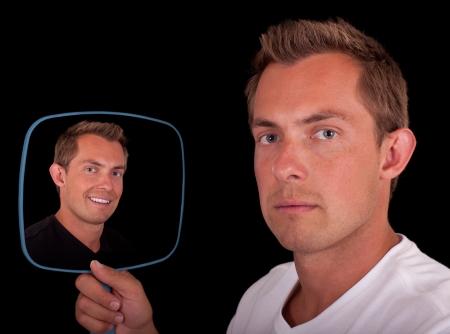 personality: retrato de un joven aislado en un fondo negro que sostiene un espejo que muestra a dos lados diferentes Foto de archivo