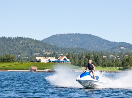 Beautiful woman out on the lake riding a wave runner on bright sunny day photo