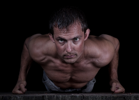 Dramatic portrait isolated on a black background of a young  male doing push-ups